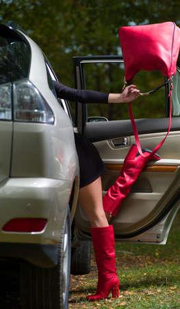 ins: Bild der weiblichen Beine mit einer Tasche in der Hand kommt ins Auto Stock Photo