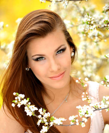 Photo of beautiful young girl on the nature of the model near the bright flowering trees