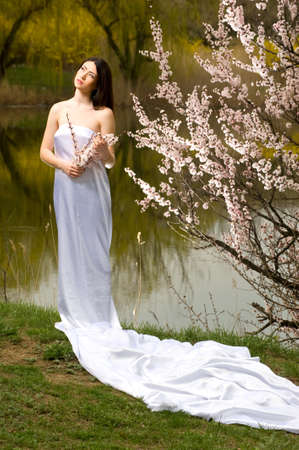 Photo sexy girl in a long dress on nature near a flowering tree Stock Photo