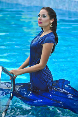 photo of a girl with beautiful make-up in a dress by the pool photo