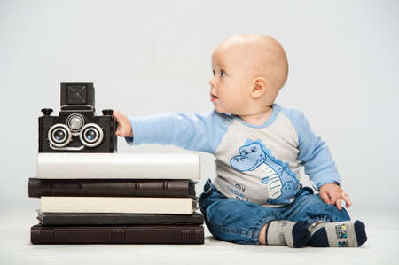 Photo of a little boy holding an old film camera