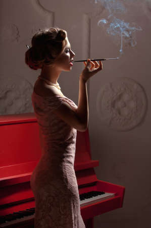 Photo of beautiful girl with make-up in a white evening dress and cigarette