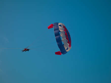photo of a man who flies on a parachute over the sea Stock Photo