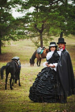 vestidos de epoca: Foto de un hombre y una mujer en un hermosos trajes de teatro al aire libre con caballos