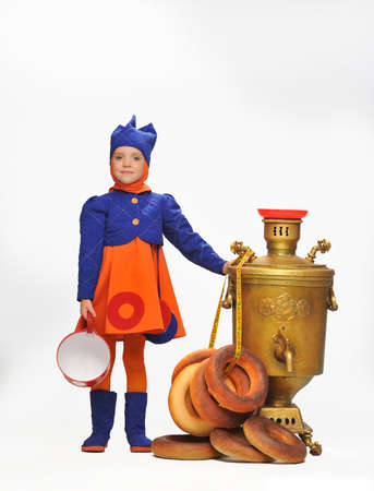 Photo of a little girl with a big samovar and bagels in the studio photo