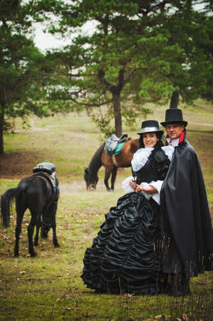 Photo of man and woman in a beautiful theater costumes outdoors with horses