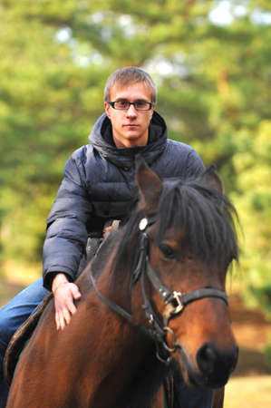 Photo of a young handsome guy riding a horse on nature stroll photo
