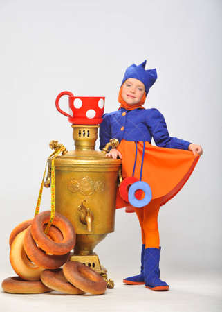 Photo  a little girl with a big samovar and bagels in the studio photo