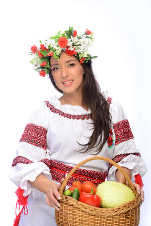 Photo of a beautiful and cute woman in Ukrainian costume with basket of vegetables