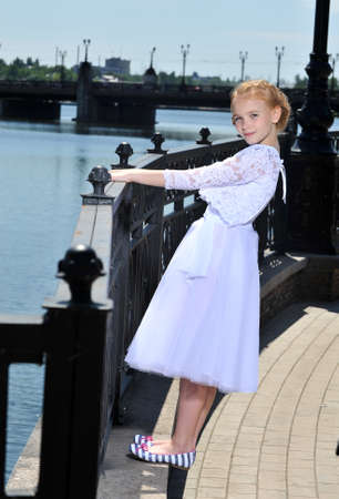 picture of a little girl in white dress posing outdoor photo