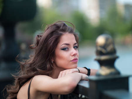Photo of a beautiful girl in the city near the river on the waterfront photo