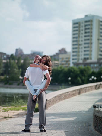 Photo girls and men on the background of the cityscape on the waterfront in the summer photo