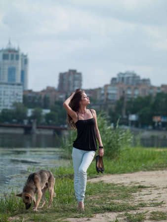 Photo of a beautiful girl and a dog in a town near the river on the waterfront photo