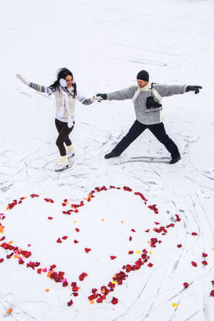 Photo of two lovers man and woman skating near the heart of rose petals on the snow photo