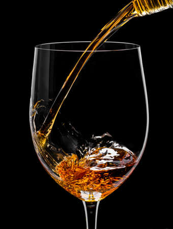 Photo of a glass of whiskey and ice on a black background