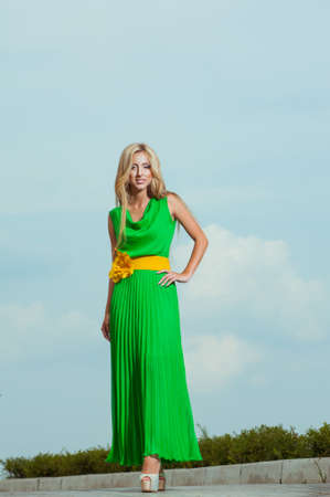 Beautiful young woman in fashionable dress greens in the city photo