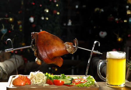 roast leg of a pig with beer on a tray