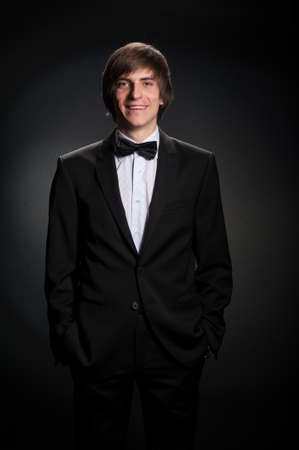 handsome young man in a strict black suit photo