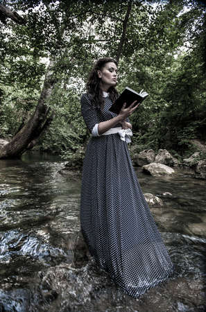 girl with a book on the river photo