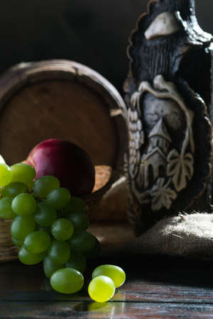 Still life of cheese, wine bottle and grapes on a background  Stock Photo