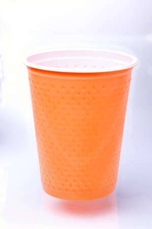 throwaway: Orange plastic cup on a white background