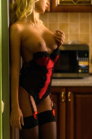 Naked woman with beautiful breasts in the kitchen