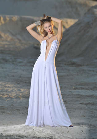 transparent dress: Lovely girl on the sand in a light transparent dress