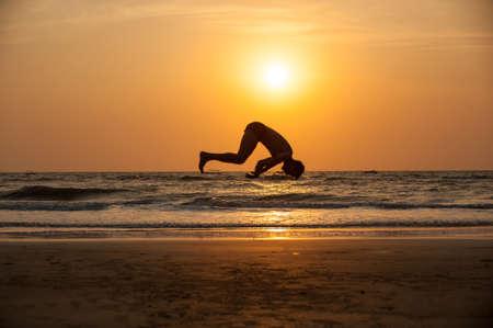 Acrobat man on the beach Stock Photo