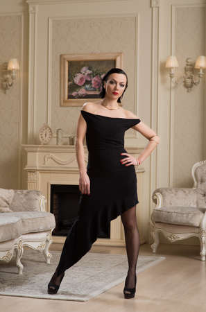 Beautiful woman in a black dress standing in the interior