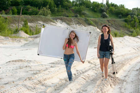 girls go over the sand with photographic equipment