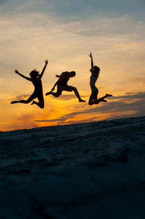 silhouette people jumping at sunset Stock Photo