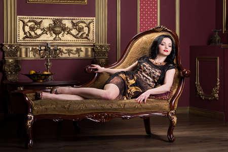 mooie vrouw op de bank in het interieur Stockfoto