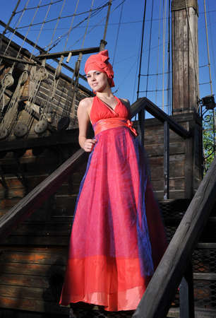 beautiful girl in a dress standing on the ship Stock Photo