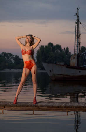 Woman in underwear on the bank of the river Stock Photo