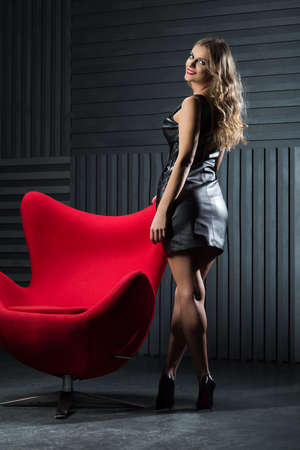 Girl in a leather dress on a red armchair Stock Photo