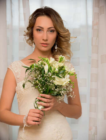 Bride with bouquet in wedding dress on window background