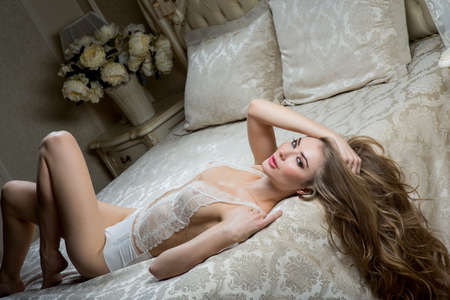 Sexy woman in a peignoir lies on a beautiful bed