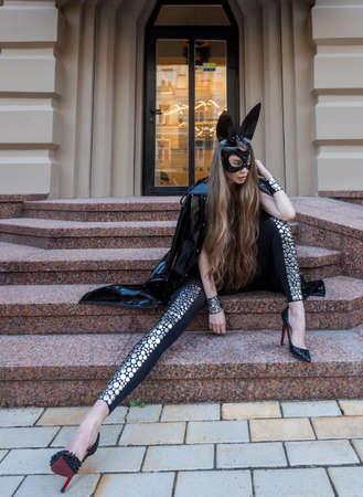 Girl in a mask near a building on the street. Reklamní fotografie