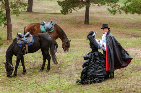 Count and countess in old outfits near the horses. Archivio Fotografico - 138943487