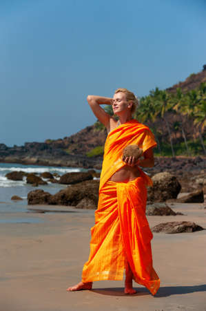 Woman in indian clothes on the beach on a background of palm trees. Stock Photo