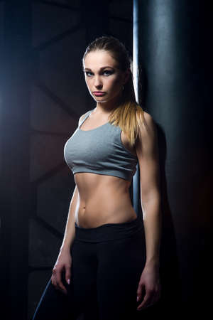 Woman with a beautiful figure in the gym near the boxing equipment.