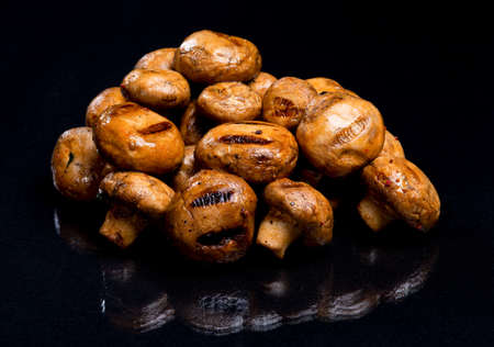 Champignon mushrooms cooked on a bonfire on a black background.