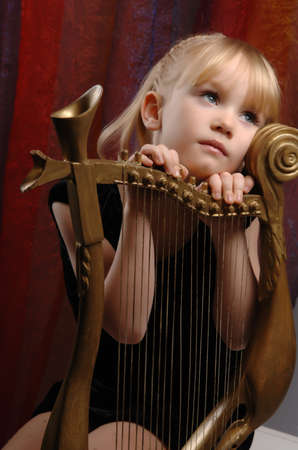 Little girl and harp musical instrument.