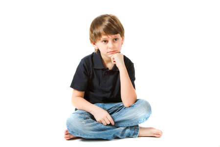 his shirt sleeves: boy sitting on the floor and thinks Stock Photo