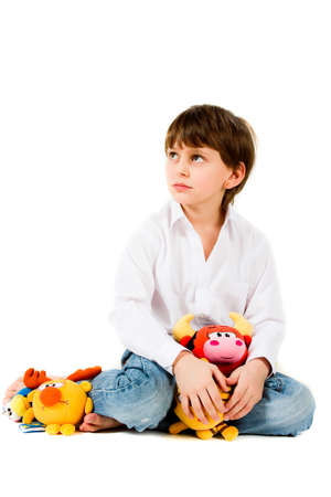 boy long hair: Boy sitting and playing soft toys Stock Photo