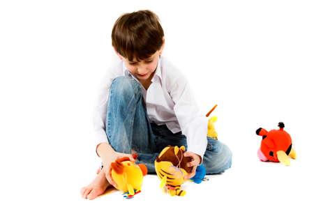 Niño sentado y jugando peluches