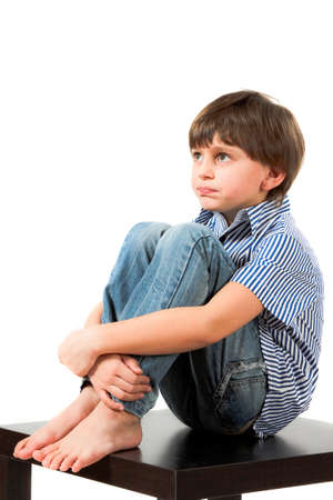 boy sitting on a table and thinking photo