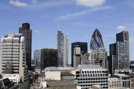 vertical buildings and gherkin against blue sky
