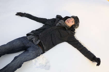 boy making snow angels Stock Photo