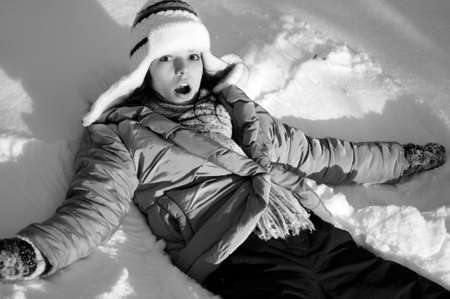 surprised girl making snow angels Stock Photo